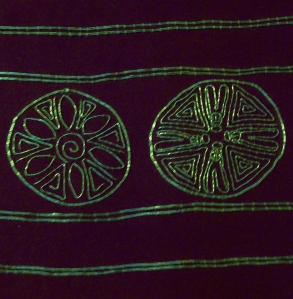 A close-up of the repeating motifs of the cuffs design; A flower in one roundel (left) and 4 bees in the other (right).
