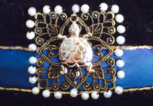 Figure 16: Close up of the front-centre filigree square, tortoise and pearls couched to the hat band.