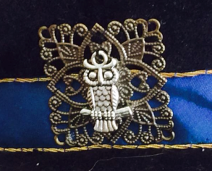 Figure 17: Close up of the owl and filigree square couched to the hat band.